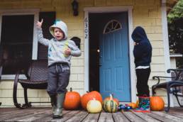 young boy exclaims animatedly on house porch