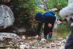young boy plays in creek