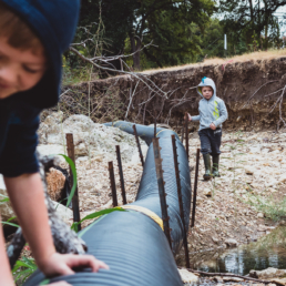 young boys play along pipe in a creek