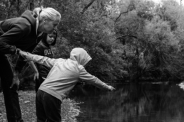 boy points out something in creek to mom and brother, in black and white