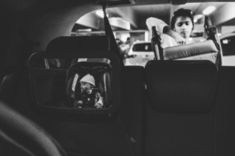 mom puts stroller in back of car while baby sleeps in car seat; in black and white