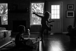 young girl dances in living room while brother watches