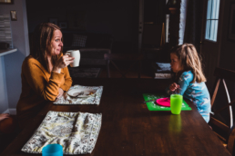 mom and daughter look at each other across kitchen table