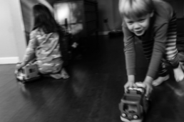 young boy runs with toy car, shows motion; in black and white