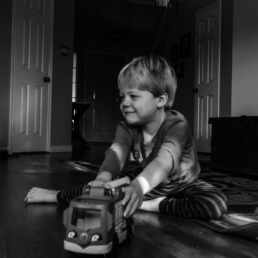 young boy plays with toy truck; in black and white