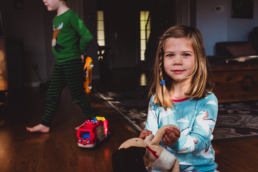 young girl plays with doll and stares at camera
