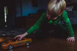 young boy plays with orange toy car