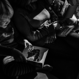 young boy reads book on couch with mom and sister