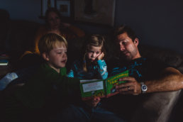 dad reads with son and daughter on couch