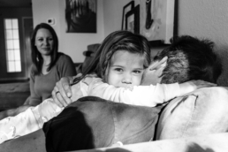 little girl hugs her dad on the couch while mom looks on