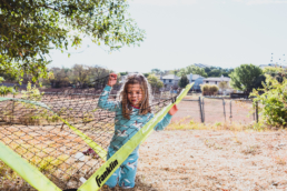 young girl plays in a soccer net