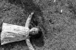 little girl lays on grass with arms spreadout and eyes closed; in black and white