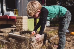 young boy plays in planter box