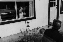 little girl stands inside her house at the window looking outside at her dad