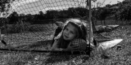 little girl rests head on soccer ball while laying in a soccer net outside; in black and white