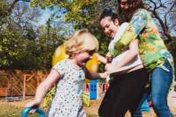 mom and daughters play outside with bouncey balls, showing motion