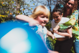 mom playfully holds teenager tight while younger daughter runs with bouncey ball