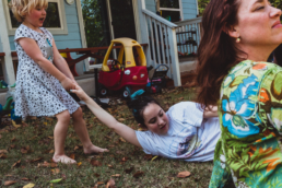 little sister drags bigger sister playfully outside