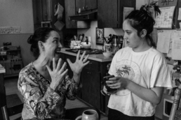 mom excitedly talks to teenage daughter in kitchen; in black and white