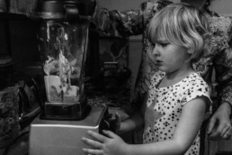 little girl looks confused as mom puts food in blender