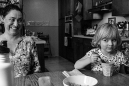 mom and daughter eat yogurt at kitchen table giving each other side eye; in black and white