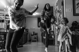 mom and daughters dance in the kitchen; in black and white