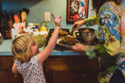 little girl raises her finger in the air while mom makes pancakes