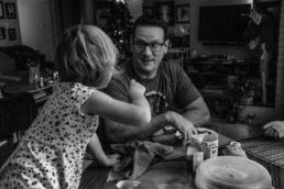 daughter talks to dad at kitchen table as he excitedly reacts; in black and white