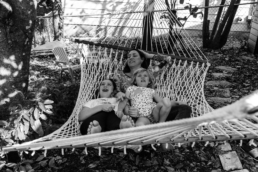 mom and daughters swing on hammock; in black and white