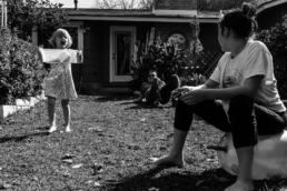 teenager sitting outside on a bouncey ball while little sister yells at her from background; in black and white