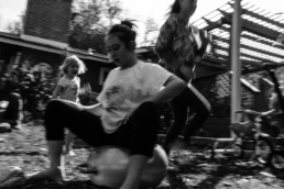 teenage girl sitting on bouncey ball while mom and sister run around her; in black and white