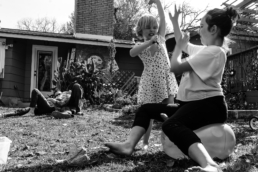 sisters outside fighting with parents relaxing in background; black and white