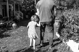dad and daughter walking outside holding hands, in black and white